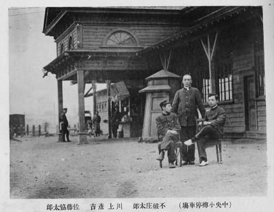 今の小樽駅の初代駅舎(撮影当時は中央小樽駅)。 3人の駅員の左後方に電話ボックスが見える。 『北海道鉄道国有紀念写真帖』 (1908=明治41年4月発行。市立小樽図書館蔵)より